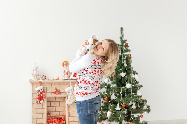 Mulher bonita com o cachorrinho engraçado jack russell terrier sobre fundo de árvore de natal