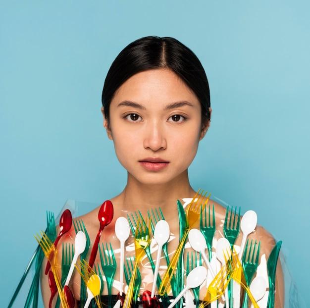 Mulher bonita com o corpo coberto por talheres de plástico coloridos