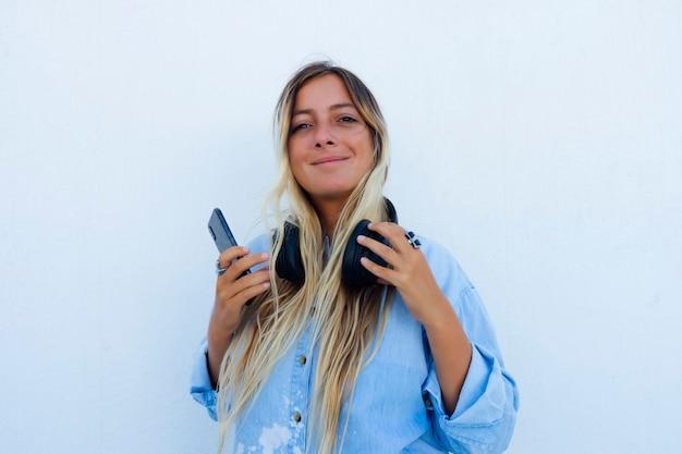 Mulher bonita com o telefone na mão ouvindo música