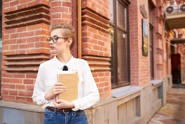 Mulher bonita com óculos andando pela cidade com uma educação literária