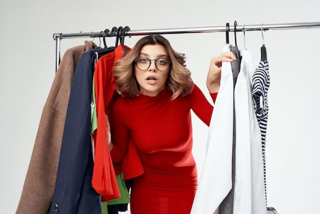 Mulher bonita com óculos ao lado de roupas, moda, emoções divertidas