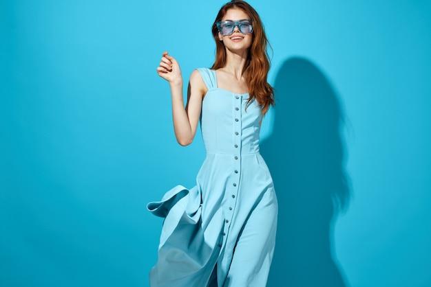 Mulher bonita com óculos da moda fundo azul estilo de vida