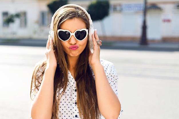 Mulher bonita com óculos de sol ouvindo música com fones de ouvido brancos