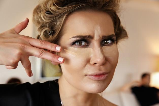 Mulher bonita com olhos escuros, maquiagem e marcador em olhos e no nariz