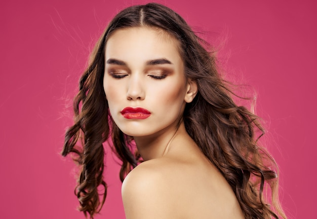 Mulher bonita com ombros nus e fundo rosa luxuoso