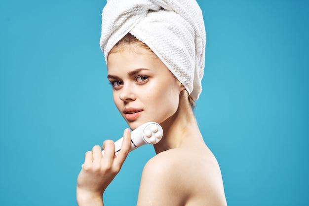 Mulher bonita com ombros nus e toalha na cabeça, massageador, rosto, pele limpa