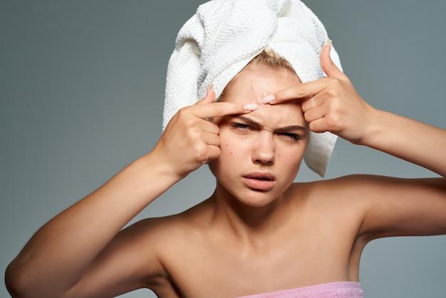 Mulher bonita com ombros nus espremendo espinhas no rosto problemas de pele
