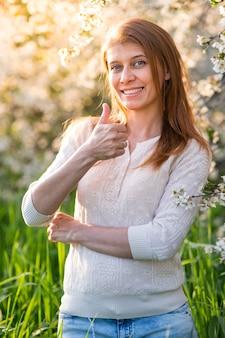 Mulher bonita com os braços cruzados sob uma árvore florida na grama verde e sob os raios do sol poente