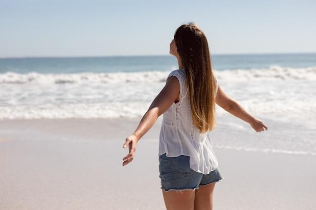 Mulher bonita com os braços esticados em pé na praia sob o sol