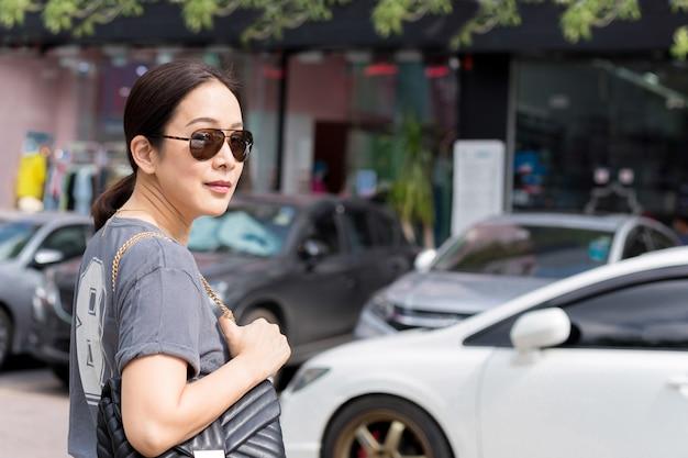 Mulher bonita com os óculos de sol na rua que olha a câmera no verão.