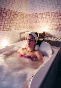 Mulher bonita com os olhos fechados, deitado na banheira, fazendo tratamento de hidroterapia. conceito de saúde e beleza.