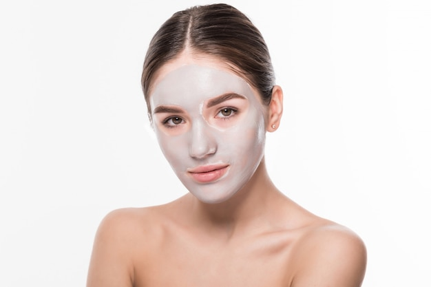 Mulher bonita com os olhos fechados e máscara facial de argila branca no rosto na parede branca
