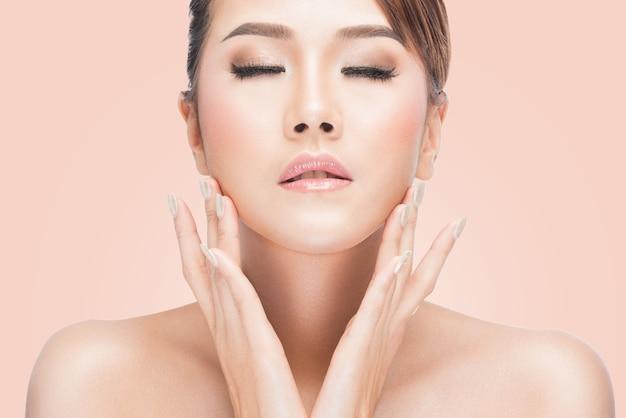 Mulher bonita com os olhos fechados que tocam em sua face sobre o fundo cor-de-rosa.
