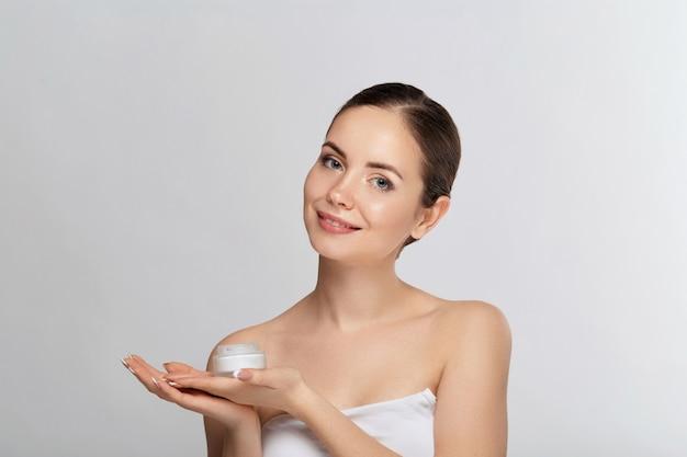 Mulher bonita com pele limpa facial lisa saudável, segurando o frasco de creme cosmético. modelo com rosto de beleza. rosto cuidados com a pele hidratante tratamento facial. cosmetologia. spa