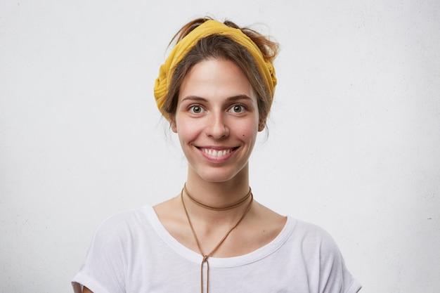Mulher bonita com pele pura, olhos escuros e sorriso agradável, com uma faixa amarela na cabeça e um pingente no pescoço