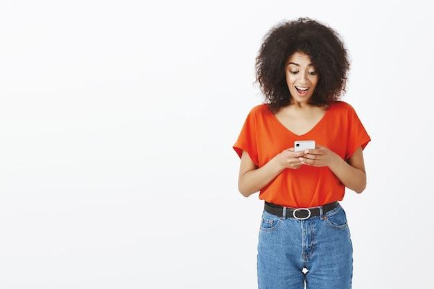 Mulher bonita com penteado afro posando com seu smartphone no estúdio