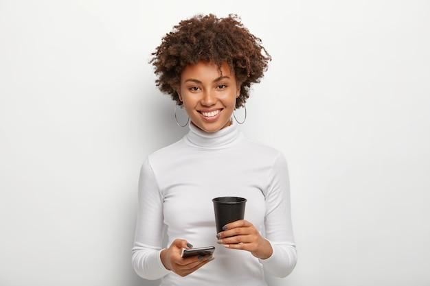 Mulher bonita com penteado afro, segura um celular moderno e café para viagem, passa o tempo livre no bate-papo online