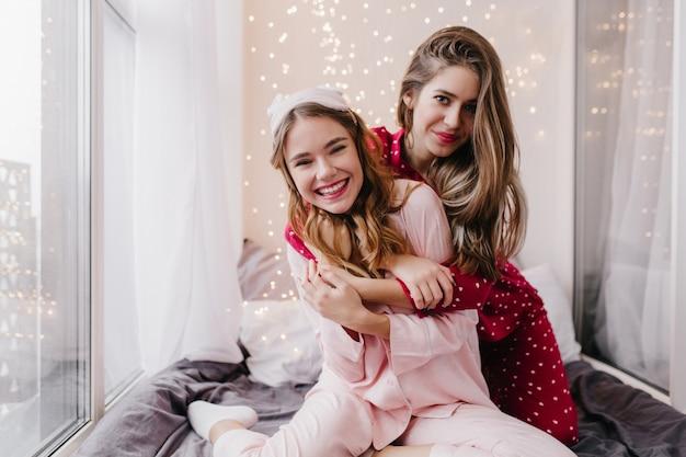 Mulher bonita com penteado comprido abraços com a irmã na manhã de fim de semana. incrível garota branca na máscara, desfrutando da sessão de fotos conjunta com um amigo.