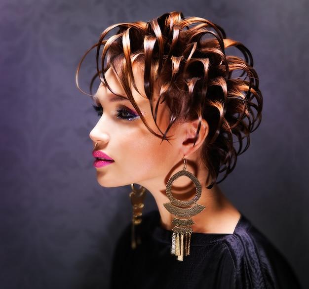 Mulher bonita com penteado da moda e maquiagem rosa brilhante posando.
