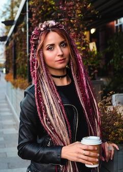 Mulher bonita com penteado de dreadlocks longos rosa em roupas pretas filmadas no outono
