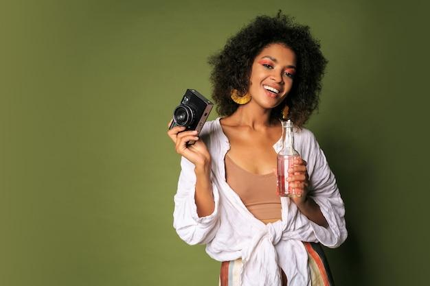Mulher bonita com penteado elegante, posando com a câmera e bebendo limonada