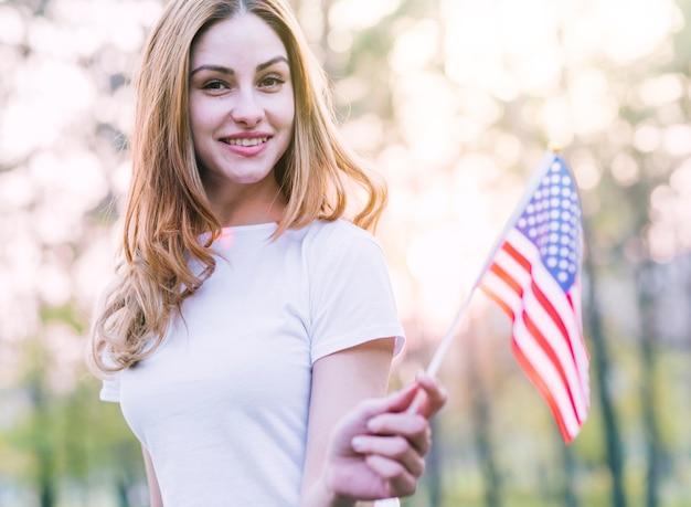 Mulher bonita com pequena bandeira americana ao ar livre