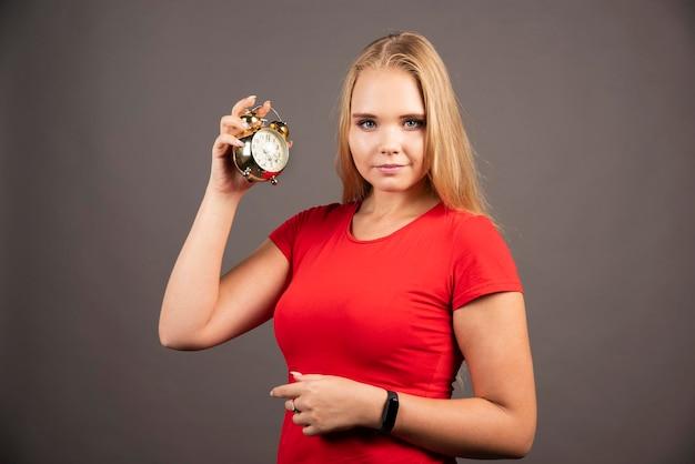 Mulher bonita com pequeno relógio de pé sobre fundo escuro. foto de alta qualidade