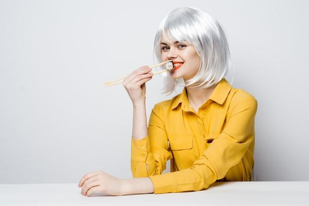 Mulher bonita com peruca branca comendo sushi em restaurante