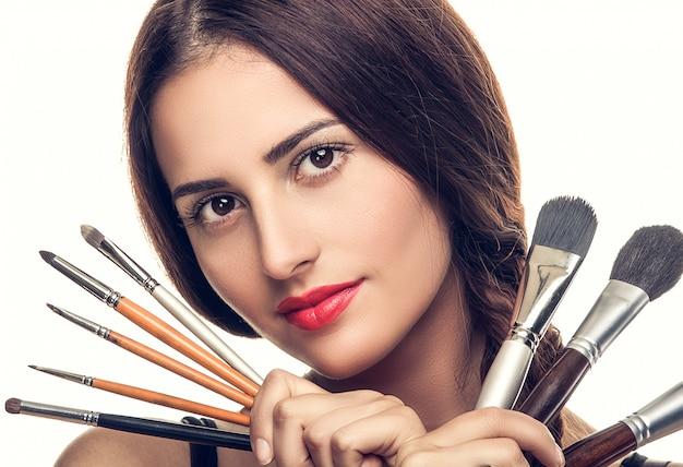 Mulher bonita com pincéis de maquiagem