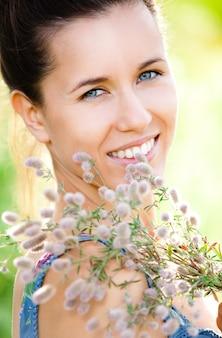 Mulher bonita com planta de campo nas mãos