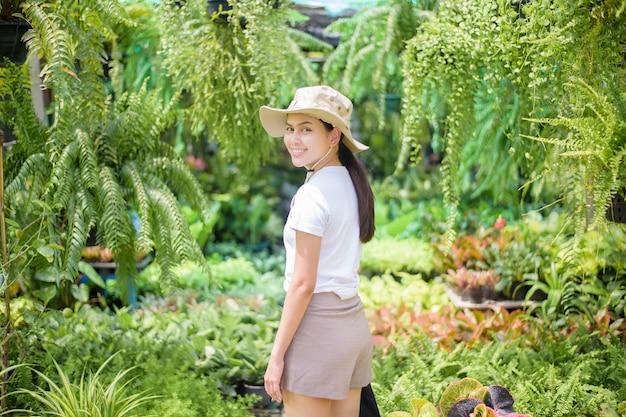 Mulher bonita com planta de jardinagem no jardim