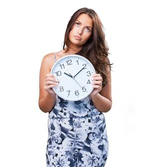 Mulher bonita com raiva segurando um relógio