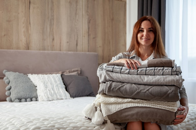 Mulher bonita com robe quente grosso de inverno está sentada e dobrando ordenadamente a roupa de cama e toalhas de banho brancas. organização e classificação da roupa limpa. têxtil de algodão orgânico e natural. fabricação.