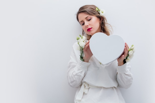 Mulher bonita com rosas brancas, vestindo uma camisa branca, segurando uma caixa de presente em forma de coração. conceito de primavera ou feriado do dia dos namorados