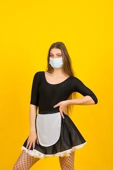 Mulher bonita com roupa de empregada, posando no estúdio com máscara protetora.