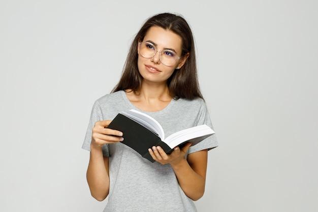 Mulher bonita com roupas casuais e óculos lendo livro