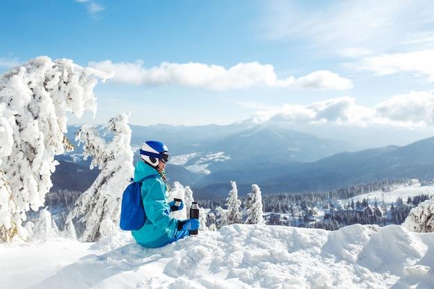 Mulher bonita com roupas de inverno, bebendo chá nas montanhas. conceito de viagem, lazer, liberdade, esporte.