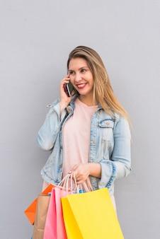 Mulher bonita com sacos de compras brilhantes, falando por telefone