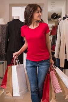 Mulher bonita com sacos de compras no shopping center