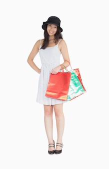 Mulher bonita com sacos de compras no vestido de bolinhas e chapéu
