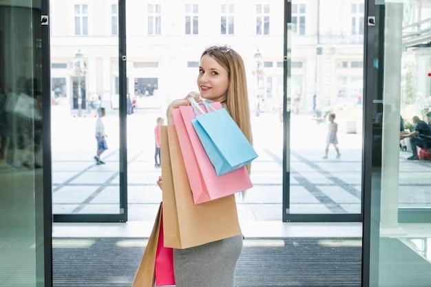 Mulher bonita com sacos de compras, olhando para a câmera