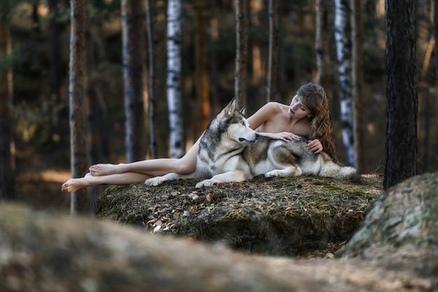 Mulher bonita com seios nus com pastor de cães na floresta