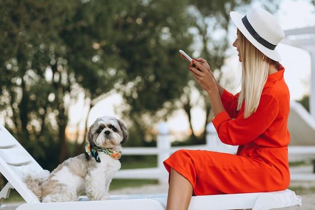 Mulher bonita com seu cachorro fofo de férias