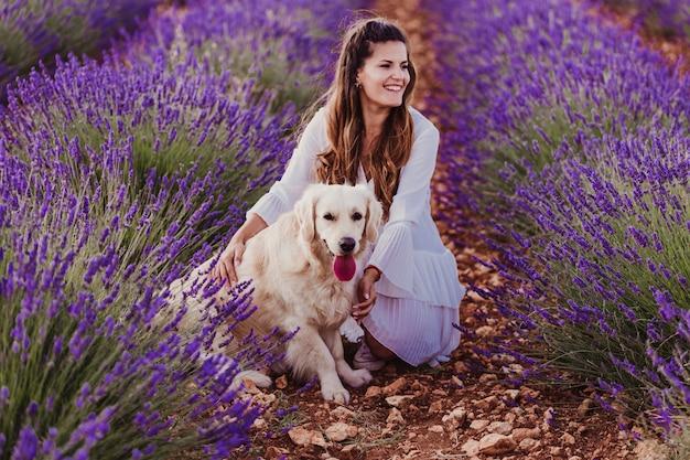 Mulher bonita com seu cachorro retriever dourado em campos de lavanda ao pôr do sol.