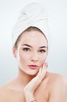 Mulher bonita com sobrancelhas escuras e ombros nus, usando uma toalha branca na cabeça e segurando uma manicure rosa
