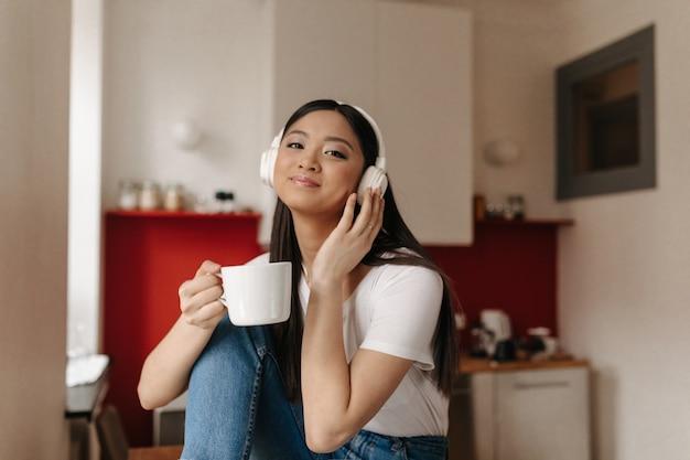 Mulher bonita com sorriso olhando para a frente, ouvindo música em fones de ouvido e segurando um copo branco no fundo da cozinha