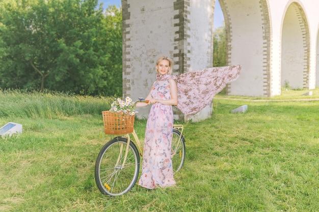 Mulher bonita com sua bicicleta no fundo do aqueduto da ponte na temporada de verão.
