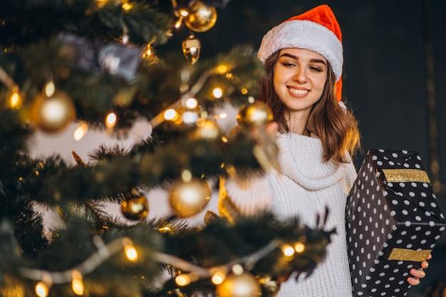 Mulher bonita com suéter quente e chapéu de natal, decorando a árvore do ano novo