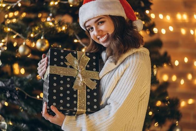 Mulher bonita com suéter quente e chapéu de natal, segurando uma caixa de gif