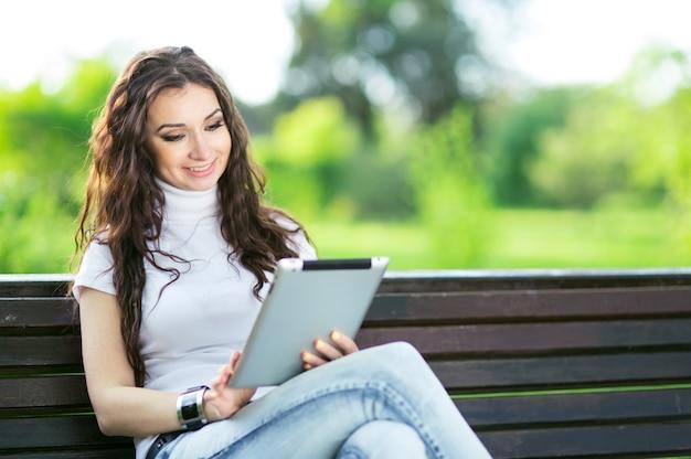 Mulher bonita com tablet no banco em green park